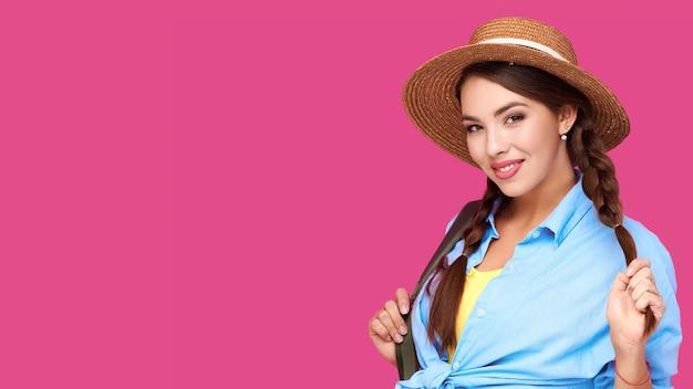 Sorridente ragazza europea che indossa abiti casual e cappello di paglia con zaino verde tenendo le trecce su vivd rosa isolare lo sfondo
