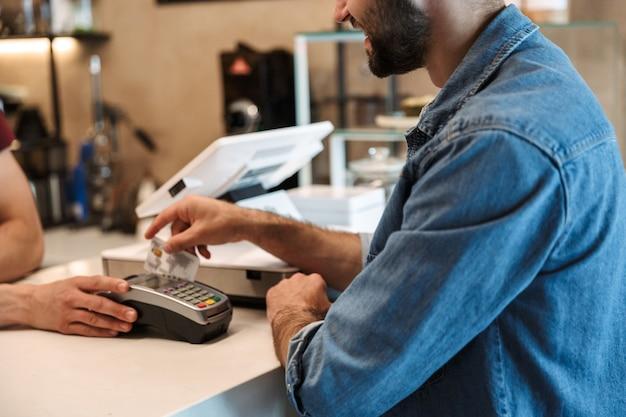 Sorridente uomo europeo che indossa una camicia di jeans pagando la carta di debito nella caffetteria mentre il cameriere tiene il terminale di pagamento