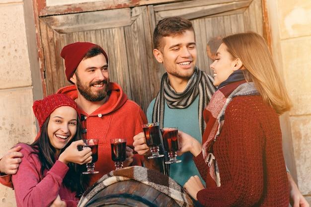Uomini e donne europei sorridenti durante il servizio fotografico di una festa. i ragazzi in posa come amici allo studio fest con bicchieri da vino con vin brulé caldo in primo piano.