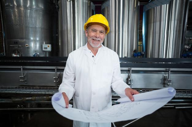 Ingegnere di fabbrica sorridente che sta nella fabbrica della bottiglia con il modello