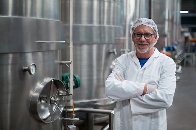 L'ingegnere sorridente della fabbrica che sta con le armi ha attraversato nella fabbrica della bottiglia