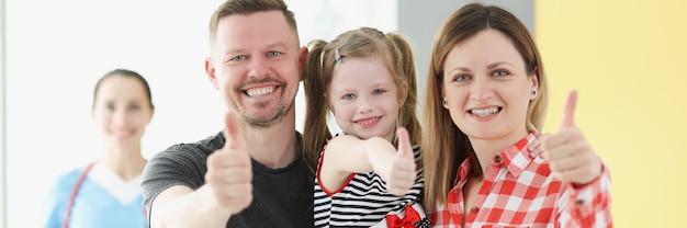 La famiglia sorridente che fa il gesto di pollice in alto in sottofondo è dottore
