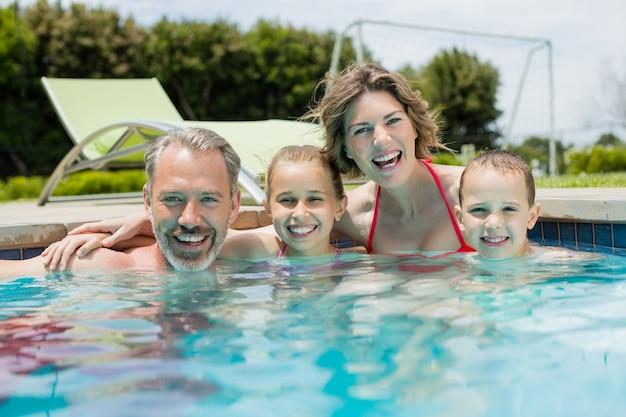 Famiglia sorridente che gode in piscina