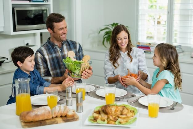 Famiglia sorridente pranzando insieme sul tavolo da pranzo