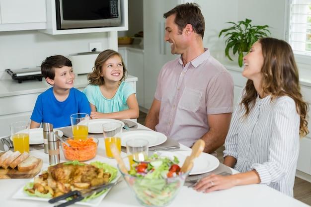 Famiglia sorridente che interagisce a vicenda mentre pranzano insieme