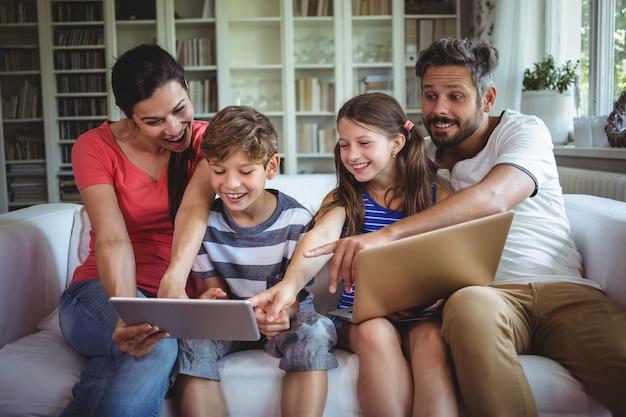 Famiglia sorridente che si siede sul sofà e che indica alla compressa digitale