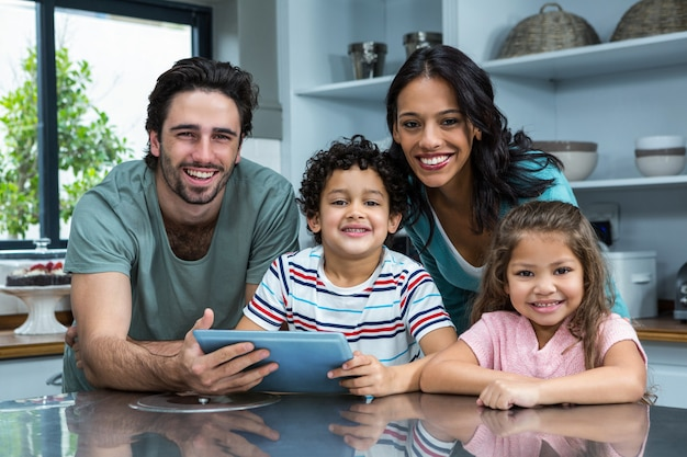 Famiglia sorridente che utilizza compressa nella cucina