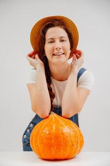 Sorridente donna contadina in una tuta di jeans e un cappello su uno sfondo bianco con una grande zucca matura