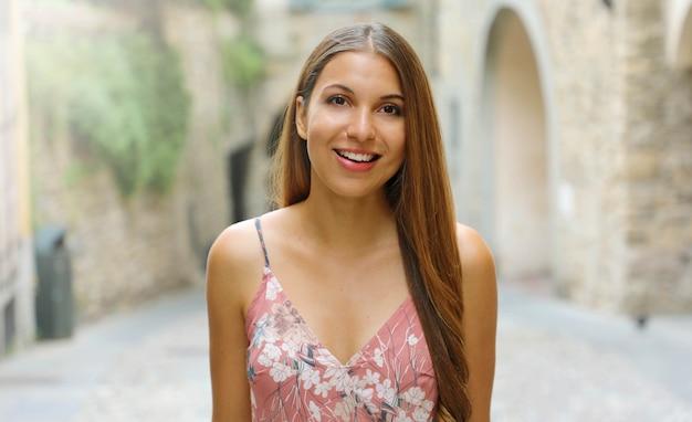 Donna vestita moda sorridente che cammina per le strade di una piccola città medievale in italia.