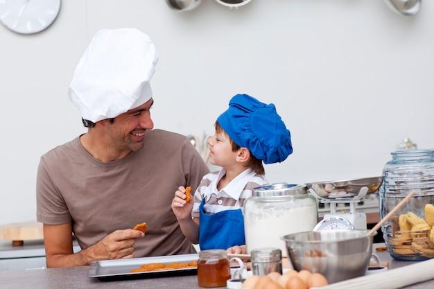 Padre e figlio sorridenti che mangiano i biscotti fatti in casa