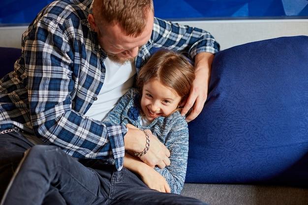 Padre sorridente con la figlia che si diverte, solletico al divano nel soggiorno, a casa
