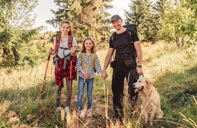 Padre sorridente con figlie e cane che fa un'escursione in montagna soleggiata