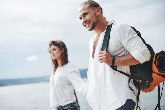 Sorridere e sentirsi felici. passeggiata allegra di coppia adorabile all'aperto sullo sfondo del lago