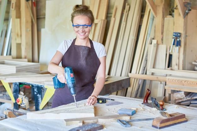 Carpentiere femminile sorridente che lavora nel negozio