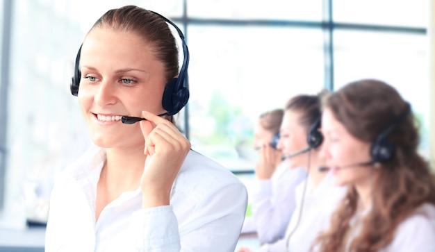 Sorridente rappresentante del servizio clienti femminile che parla in cuffia con i colleghi in background in ufficio