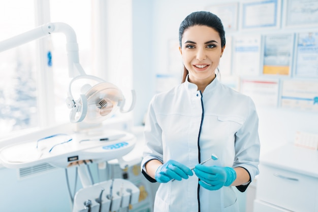Dentista femminile sorridente in uniforme e guanti, clinica dentale, odontoiatria pediatrica professionale, stomatologia dei bambini