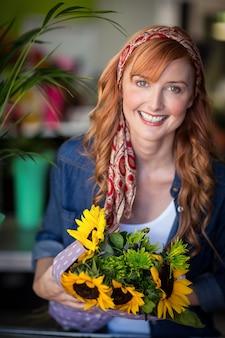 Fiorista femminile sorridente che tiene mazzo di fiore
