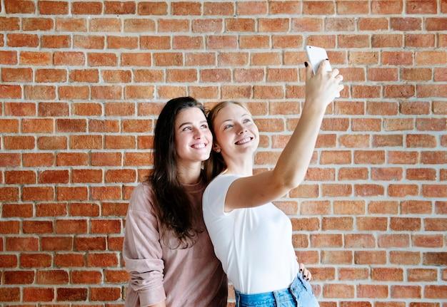 Amici femminili sorridenti che prendono un selfie