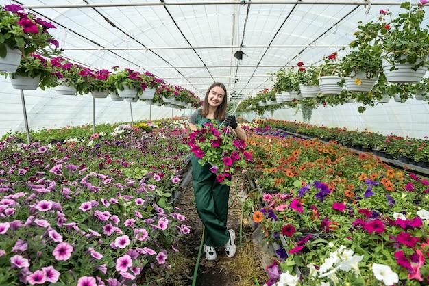 Sorridente giardiniere femminile che lavora con i fiori in una serra. tempo di primavera