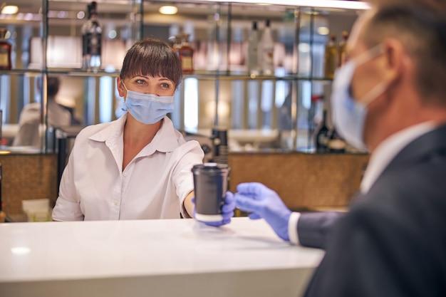 La donna sorridente tiene in mano una tazza di caffè per un uomo elegante al bar mentre indossa maschere e guanti di sicurezza