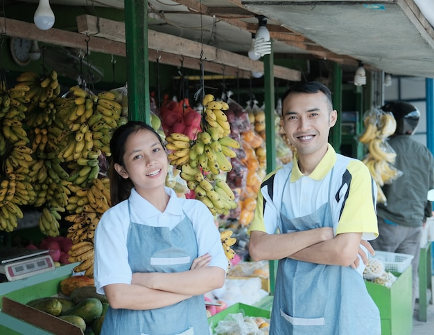 Sorridente negoziante maschio e femmina in grembiule in piedi con le mani incrociate nel mercato della frutta