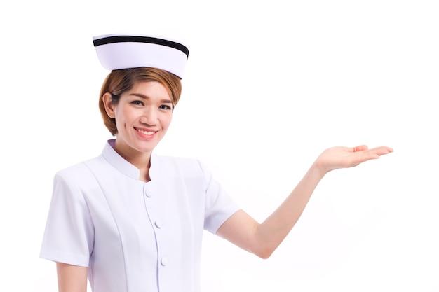 Infermiera femminile sorridente che presenta, indicando la sua mano allo spazio vuoto