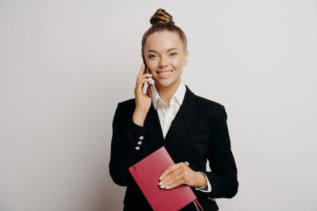 Impiegata femminile sorridente, donna in costume nero formale che ha conversazione telefonica, tiene in mano un taccuino rosso con dati, sente buone notizie mentre si trova in piedi isolato su sfondo grigio