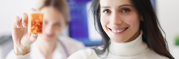 Paziente femminile sorridente che tiene le pillole sullo sfondo del dottore
