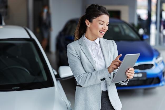 Venditore femminile sorridente in vestito facendo uso della compressa per cercare quale automobile è venduta mentre levandosi in piedi nel salone dell'automobile.