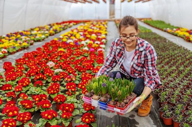 Proprietario di piccola impresa femminile sorridente che si accovaccia e che tiene cassa con i fiori sta per sistemarlo in fila