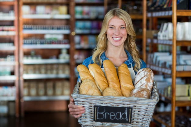 Personale femminile sorridente che tiene un cestino dei pani