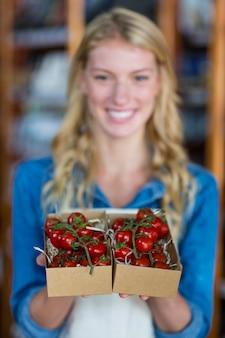 Scatola sorridente della tenuta del personale femminile di pomodoro ciliegia nel supermercato