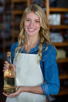 Il personale femminile sorridente che tiene l'olio d'oliva imbottiglia il supermercato