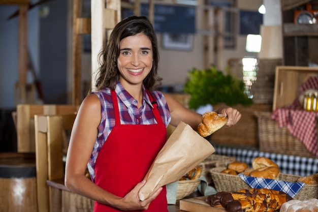 Personale femminile sorridente che imballa cibo dolce in sacchetto di carta al bancone in panetteria