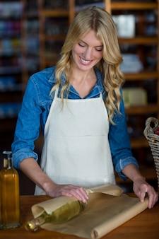 Personale femminile sorridente che avvolge la bottiglia di olio d'oliva con carta marrone