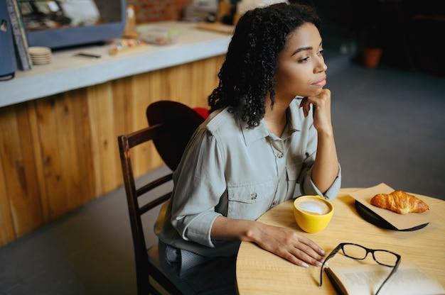 Sorridente studentessa beve caffè con croissant nella caffetteria