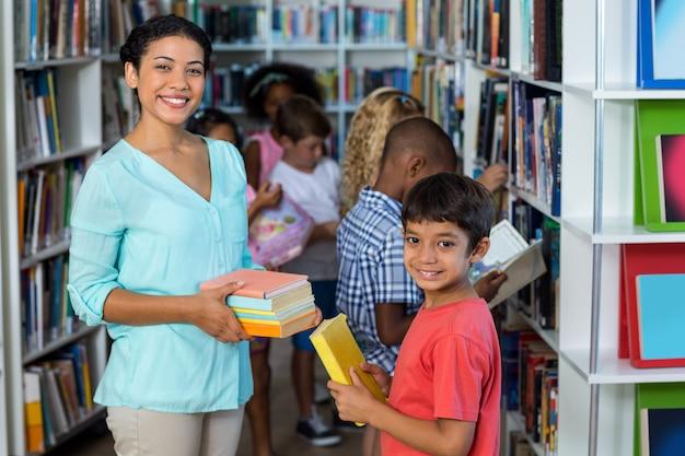 Insegnante femminile sorridente che dà i libri al ragazzo