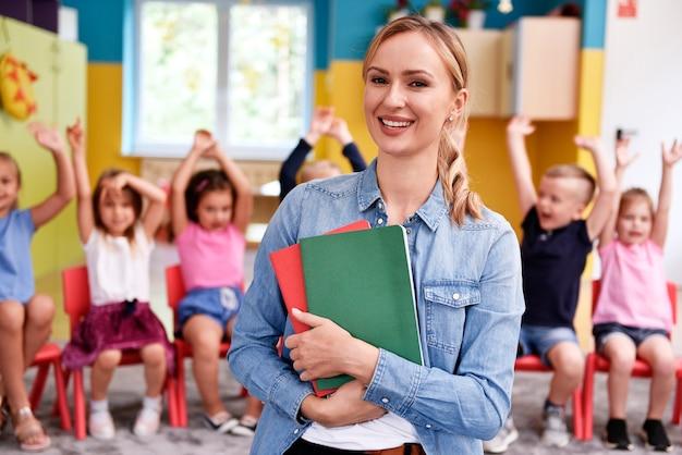 Insegnante femminile sorridente nella scuola materna