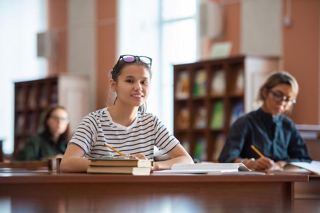 Adolescente femminile sorridente in abbigliamento casual che ti guarda mentre è seduto alla scrivania nella biblioteca del college e prepara il compito a casa