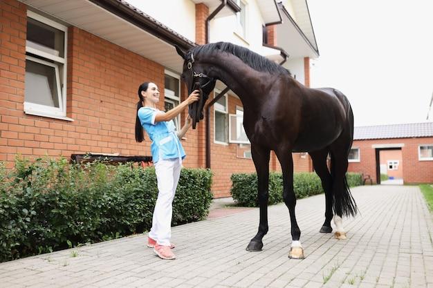 Il veterinario femminile sorridente conduce l'esame fisico dell'assistenza sanitaria per gli animali del cavallo nero