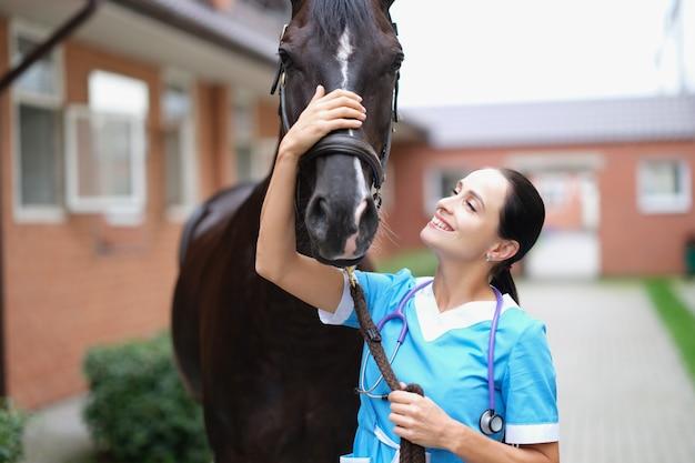 Veterinario femminile sorridente che accarezza il primo piano del cavallo nero