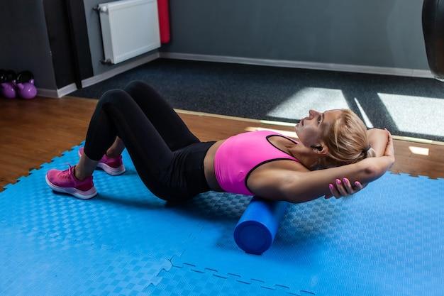 Donna in forma sorridente che massaggia la schiena con un rullo massaggiante dopo un duro allenamento in classe di fitness