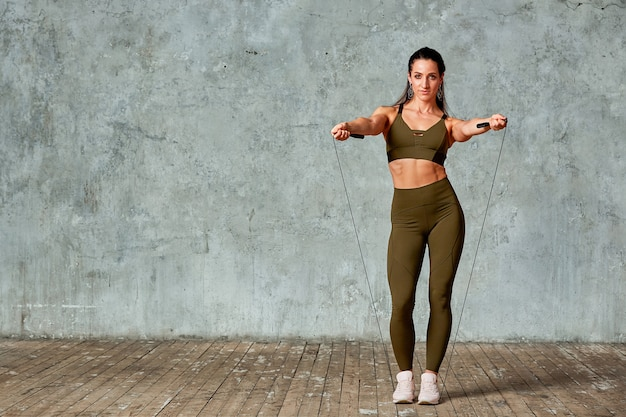 Posa di modello sorridente di forma fisica nella palestra integrale contro una parete grigia con i saltatori in sue mani, concetto di forma fisica