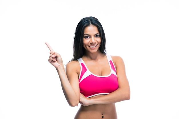 Sorridente donna fitness puntare il dito verso l'alto