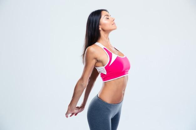 Sorridente donna fitness allungando le mani