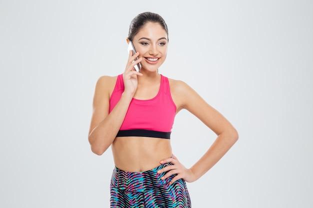 Donna fitness sorridente che parla al telefono