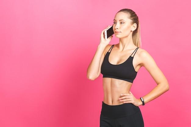 Sorridente donna fitness utilizza lo smartphone isolato su uno sfondo rosa