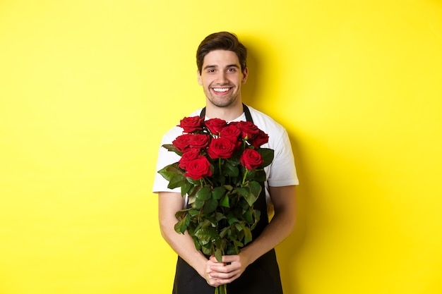 Fiorista sorridente in grembiule nero con fiori, vendita di bouquet di rose, in piedi sul giallo