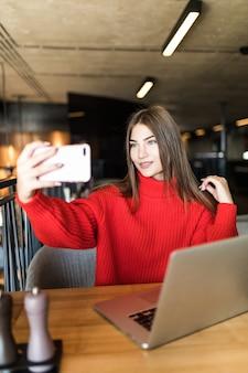 Una donna freelance sorridente si fa un selfie al telefono o fa una videochiamata, una giornata lavorativa di una giovane donna libera o di uno studente con un laptop.