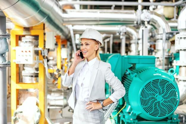 Sorridente imprenditrice amichevole con il casco sulla testa in piedi nella centrale elettrica con la mano sul fianco e parlando con il partner commerciale al telefono.